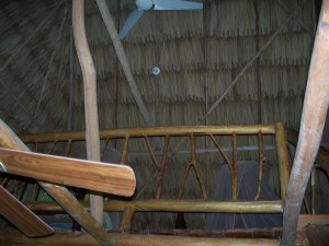 Two beds upstairs, ceiling fans, and thatched roof